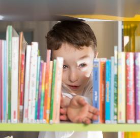 enfant derrière une étagège de livres